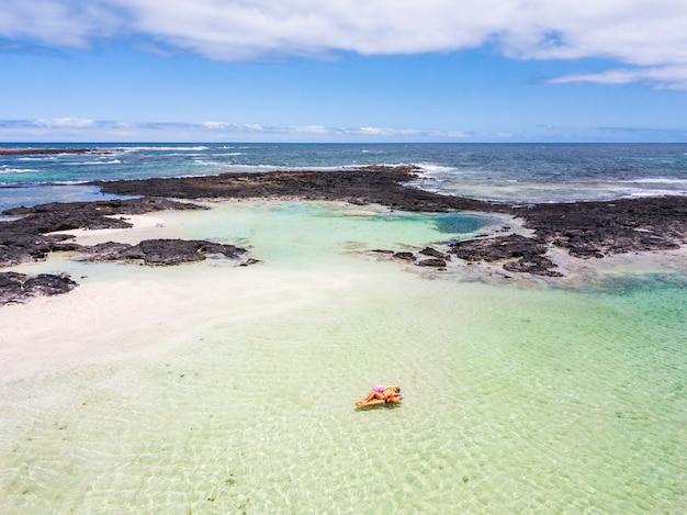 Vue ci-dessus pour le concept de vacances de voyage et de vacances d'été - une belle femme caucasienne s'allonge sur un lilo à la mode et se détend sur une eau turquoise de l'océan dans une plage de lagon comme un paradis