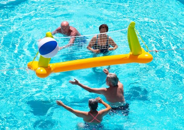 Vue ci-dessus de quatre personnes âgées jouant au volley-ball dans l'eau de la piscine été et vacances