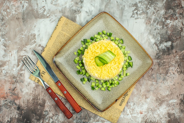 Vue ci-dessus d'une savoureuse salade servie avec du concombre haché et une fourchette de couteau sur un vieux journal sur fond de couleur mélangée