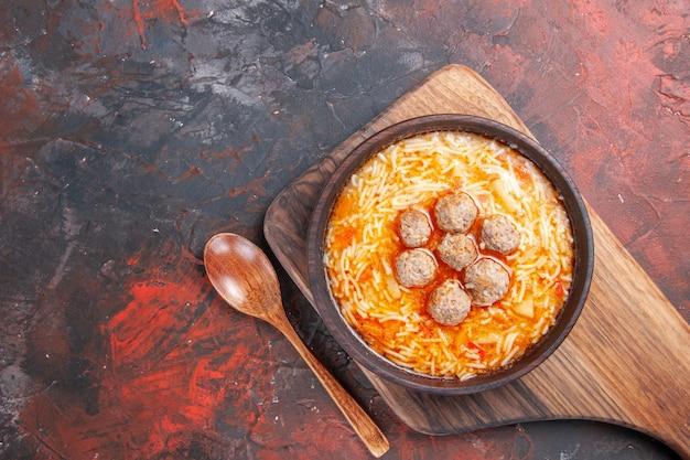 Vue ci-dessus d'une savoureuse soupe de boulettes de viande avec des nouilles sur une planche à découper en bois et une cuillère sur fond sombre