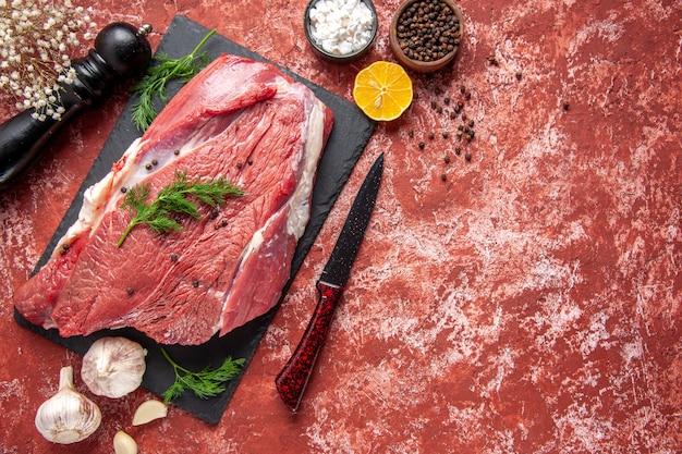 Vue ci-dessus de la viande rouge fraîche crue avec du vert et du poivre sur un tableau noir couteau marteau en bois sel citron sur fond rouge pastel à l'huile