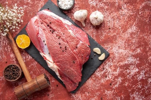 Vue ci-dessus de la viande rouge fraîche avec du poivre sur un tableau noir couteau ail épices citron marteau en bois marron citron sur fond rouge pastel à l'huile