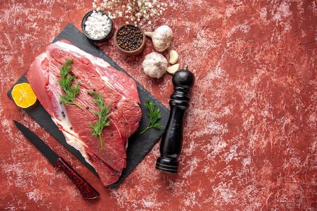 Vue ci-dessus de la viande rouge fraîche avec du vert et du poivre sur un tableau noir couteau ail citron épices marteau en bois citron sur le côté droit sur fond rouge pastel à l'huile
