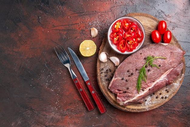Vue ci-dessus de la viande rouge sur un plateau en bois et de l'ail vert haché poivre bouteille d'huile tombée fourchette et couteau sur table sombre