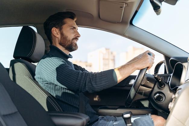 Vue en contre-plongée de l'homme sérieux et confiant qui monte dans la voiture et regarde la route pendant la conduite. stock photo