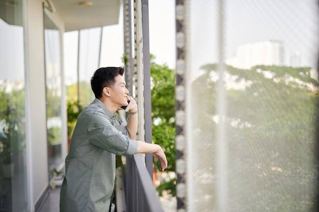 Vue en contre-plongée d'un jeune homme souriant parlant au téléphone portable, debout sur la terrasse du balcon
