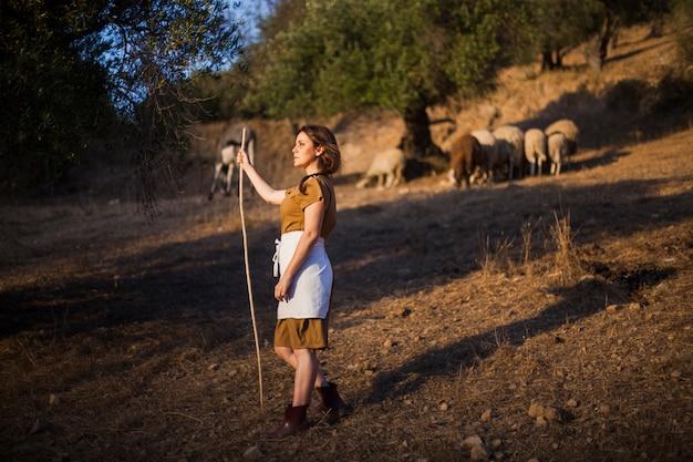 Vue de côté de l'agricultrice tenant un bâton dans le champ