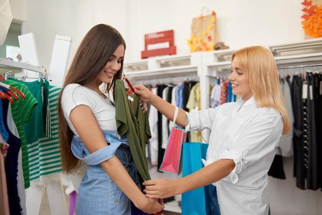 Vue de côté des amies shopping ensemble dans les magasins