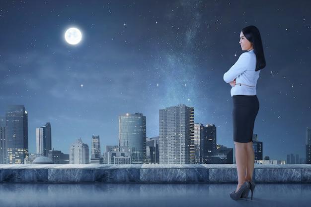 Vue côté, de, asiatique, femme affaires, debout, sur, terrasse, regarder, cityscape