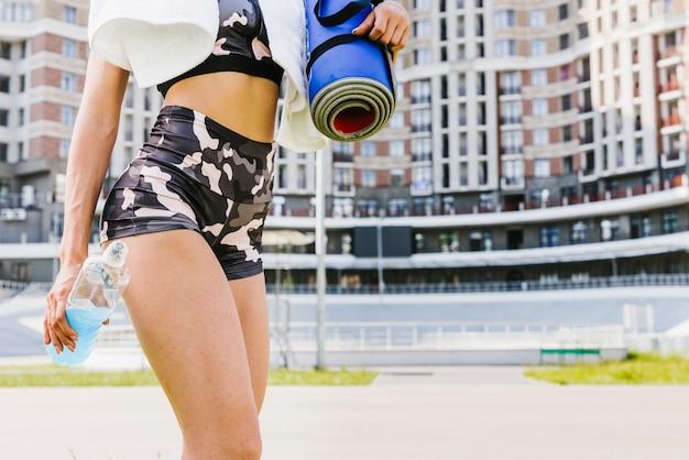 Vue de côté de l'athlète avec tapis de yoga