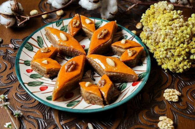 Vue de côté baklava azerbaïdjanais traditionnel sur une assiette avec des fleurs sur la table