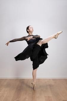 Vue de côté ballet une jambe en l'air pose