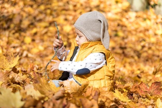 Vue de côté bébé avec chapeau jouant à l'extérieur
