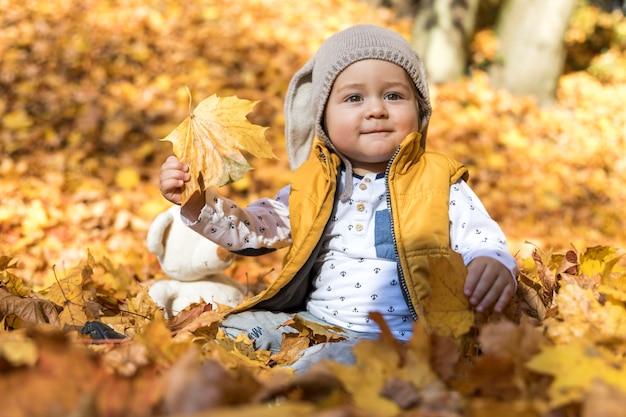 Vue de côté bébé mignon jouant avec des feuilles