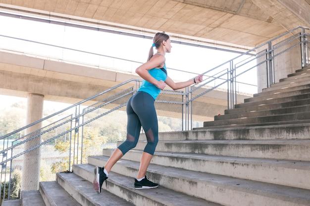 Vue de côté d'une belle athlète en cours d'exécution dans l'escalier