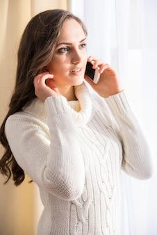 Vue de côté de la belle femme parle au téléphone.