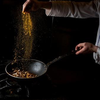 Vue côté, champignon, friture, à, poêle, et, épice, et, main humaine, dans, casserole