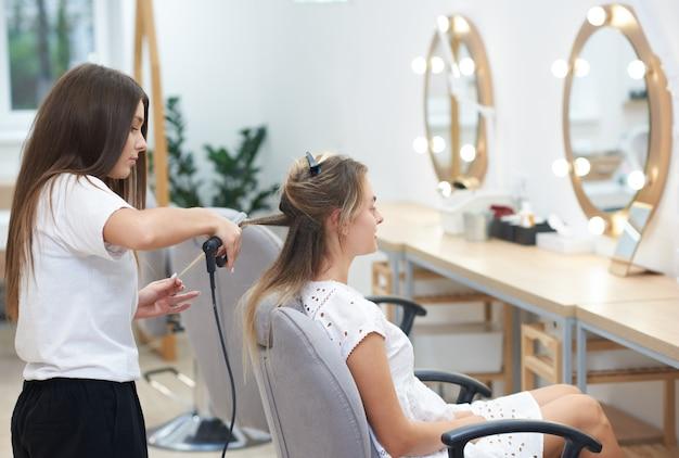 Vue, côté, coiffeur, sertissage, cheveux, client, ondulé, fer