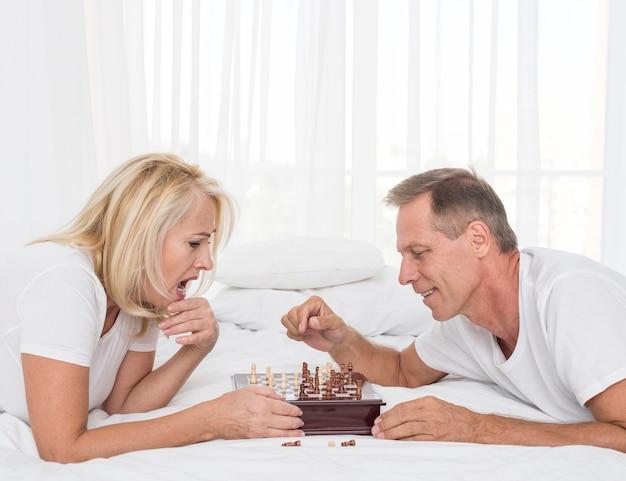 Vue côté, couple, jouer échecs, dans chambre à coucher