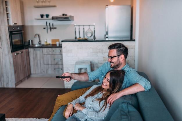 Vue de côté d'un couple en regardant un film à la maison.