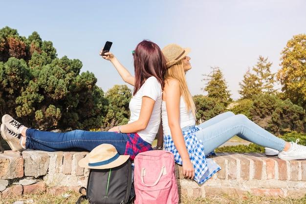 Vue de côté de deux amies assis dos à dos prenant selfie sur téléphone portable