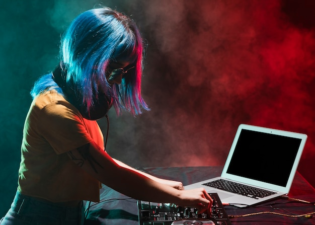 Vue de côté dj féminin en mixage club