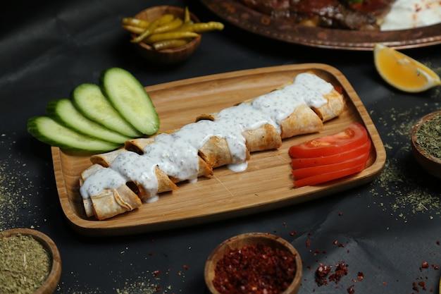 Vue de côté doner dans du pain pita avec du yaourt, tomates et concombres aux épices sur un plateau