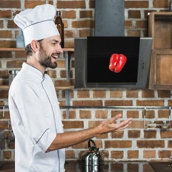 Vue de côté du chef masculin jetant le poivron rouge dans l'air