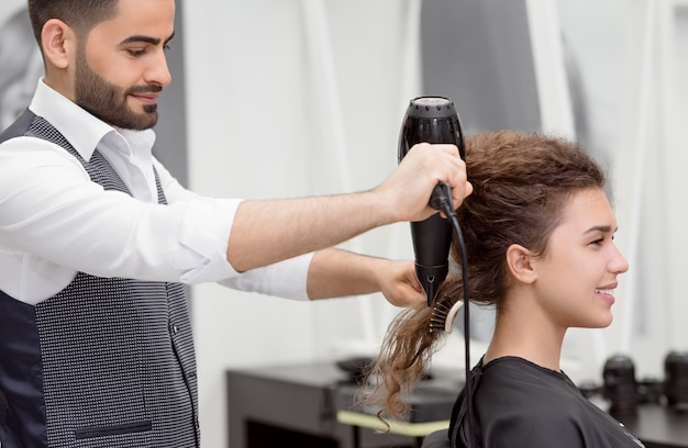 Vue de côté du coiffeur arabe séchant les cheveux bouclés de la cliente souriante.