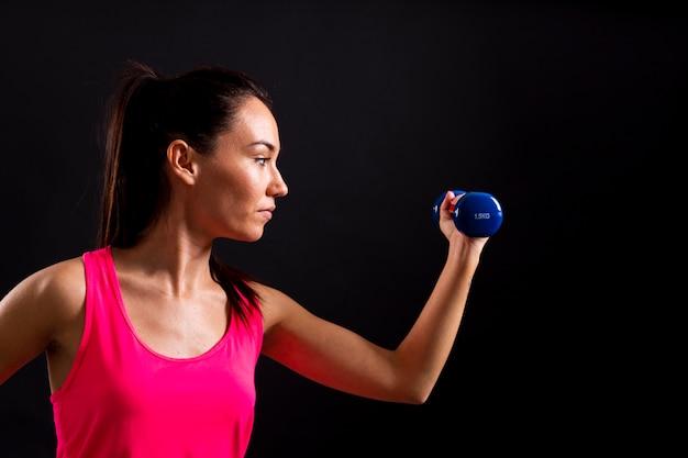 Vue de côté de l'exercice féminin avec des poids