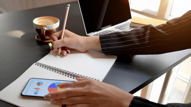 Vue côté, de, femme affaires, écriture, sur, cahier, quoique, regarder, diagramme affaires, dans, confortable, lieu de travail