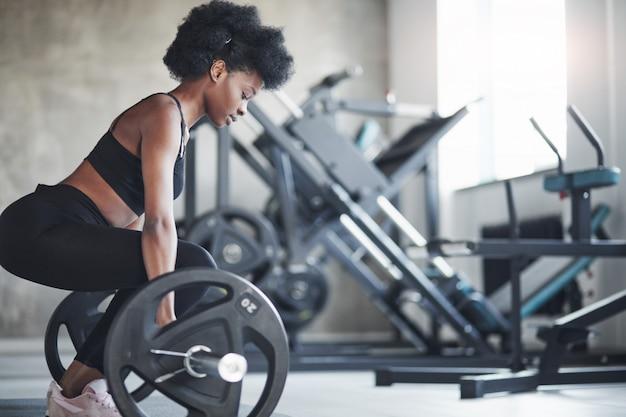Vue de côté. femme afro-américaine aux cheveux bouclés et en vêtements sportifs ont une journée de remise en forme dans la salle de sport