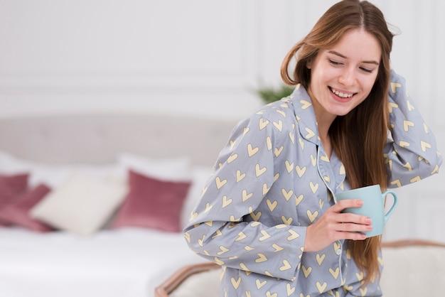 Vue côté, femme, chez soi, boire thé