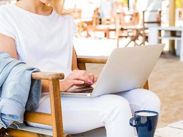 Vue côté, de, femme, dehors, dans chaise, travailler, ordinateur portable