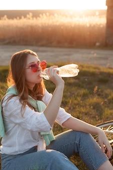 Vue côté, de, femme, eau potable, dans, les, coucher soleil