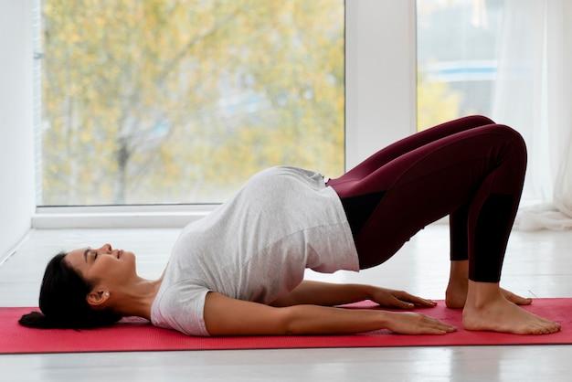 Vue côté, femme enceinte, faire, yoga, intérieur