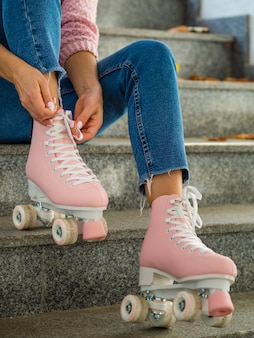 Vue côté, de, femme, sur, escalier, attacher, lacet, sur, patins a roulettes