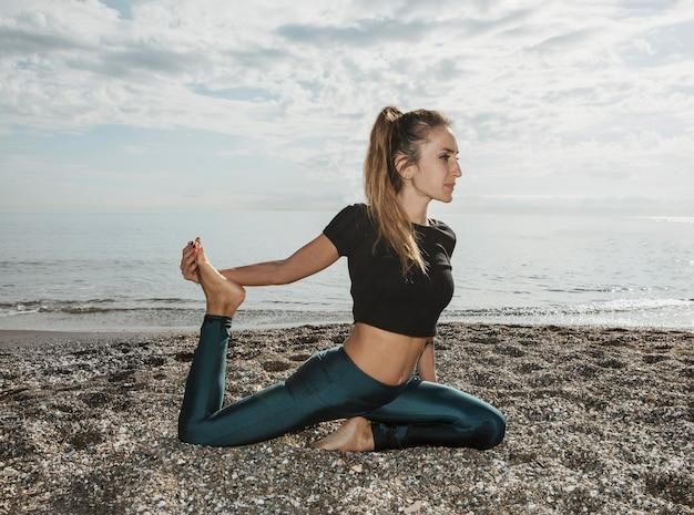 Vue côté, de, femme, étirage, elle, jambe, pendant, yoga, plage