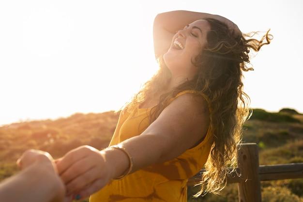 Vue côté, de, femme heureuse, tenant mains, à, photographe