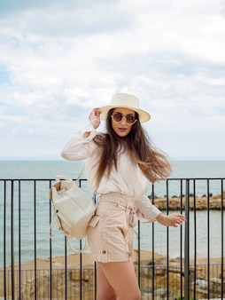 Vue côté, femme, à, lunettes soleil, et, chapeau