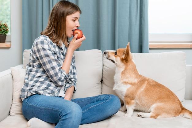 Vue côté, de, femme mange, pomme, sur, divan, à, chien