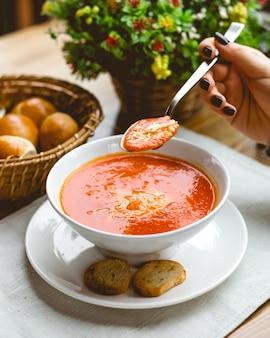 Vue côté, femme, manger, tomate, soupe, râpé, fromage, et, craquelins