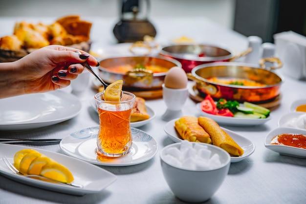 Vue côté, femme, mettre, dans, tasse thé, tranche citron, crêpes, à, oeufs durs, tomates, concombres, et, miel, table, servir, petit déjeuner