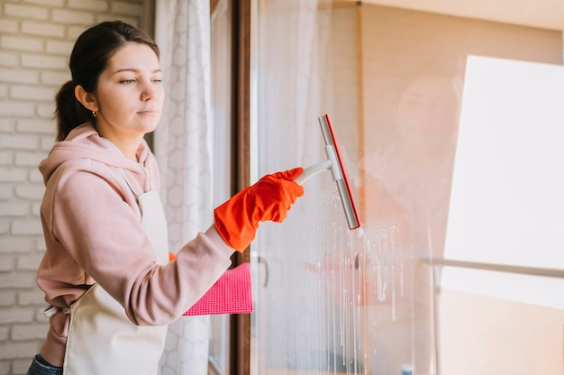 Vue côté, femme, nettoyage, fenêtre