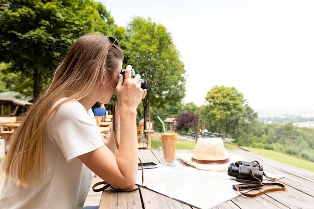 Vue de côté d'une femme prenant une photo
