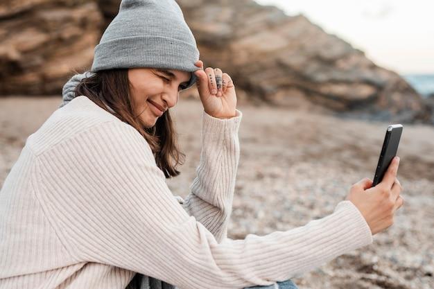 Vue côté, de, femme prenant selfie, plage