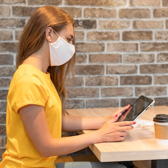 Vue côté, femme, à, tablette, porter, masque