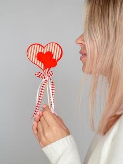Vue côté, femme, tenue, coeur papier