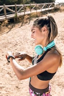 Vue de côté femme vérifiant l'heure sur smartwatch