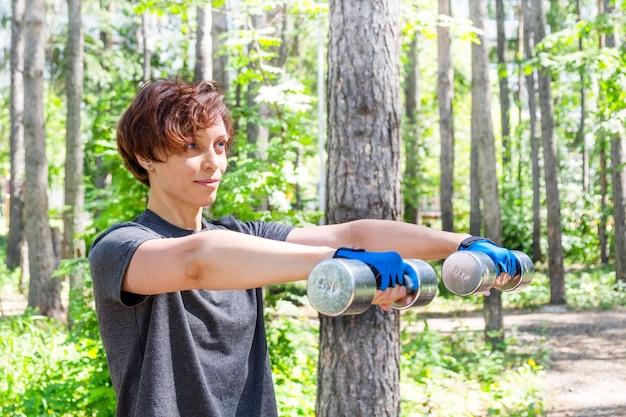 Vue de côté de fille de formation de remise en forme exercice d'entraînement des bras avec des haltères